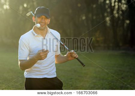 Portrait of cheerful golf player with putter and ball.