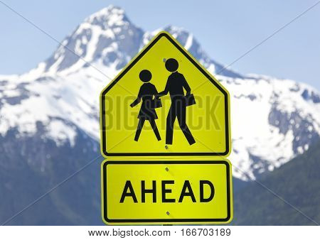 The warning sign about people ahead on Skagway town street.