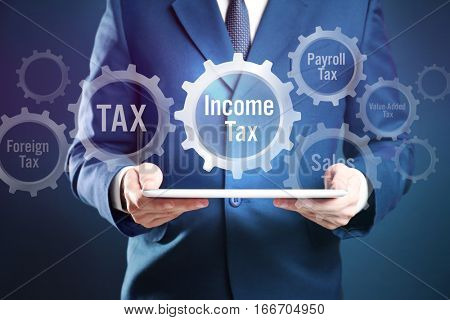Man holding tablet and gear wheel with text INCOME TAX. Taxation concept