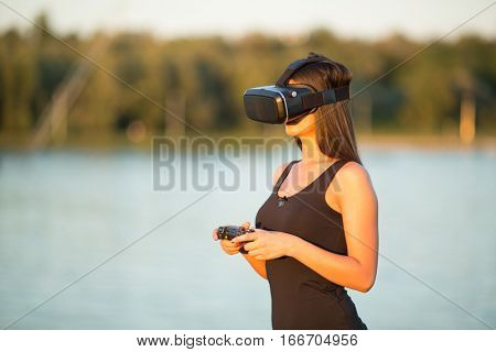 beautiful woman  with virtual reality in outdoor park. VR headset glasses device. nature outdoors background. people and technology concept
