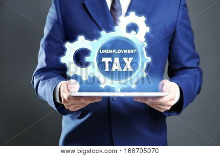 Man holding tablet and gear wheel with text UNEMPLOYMENT TAX. Taxation concept