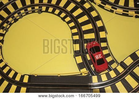 Car track a child's toy. Race track with rails and a red car. Black stripes on yellow.