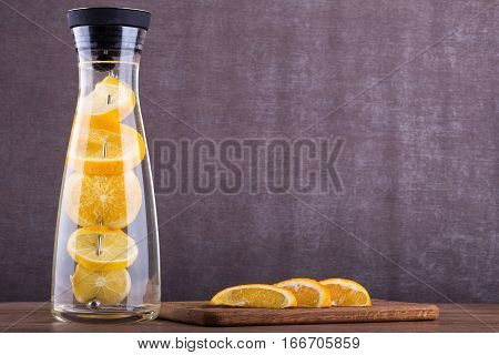 Refreshing water with orange. Orange slices a in water. Drink in a glass jar. Homemade lemonade on wooden background.