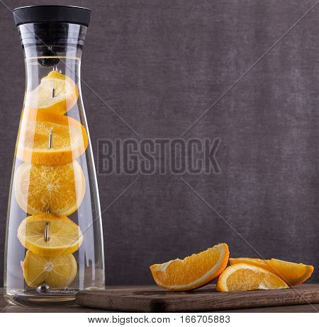 Refreshing water with orange . Orange slices a in  water. Drink in a glass jar. Homemade lemonade  on wooden background. Drinks for a party. Summer drink.