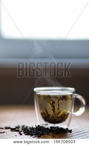 Hot steamy green tea in front of a window glass
