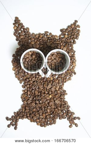 Roasted grains of black coffee. The grains are scattered in the form of an owl figurines. Owl Eyes in the form of two white cups and pour them coffee beans.