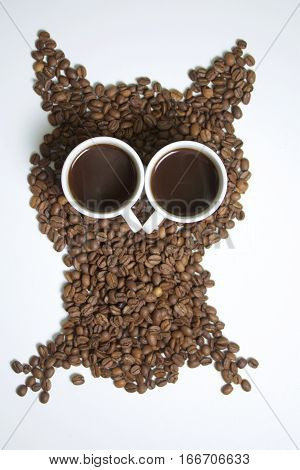 Roasted grains of black coffee. The grains are scattered in the form of an owl figurines. Owl Eyes in the form of two white cups of brewed coffee is poured into them.