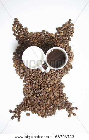 Roasted grains of black coffee. The grains are scattered in the form of an owl figurines. Owl Eyes in the form of two white cups. One of them poured brewed coffee. In another milk.