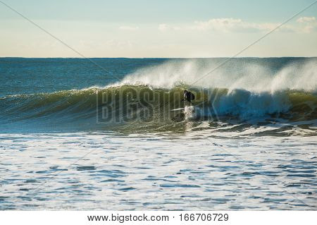 Surfer ducking under the wave lip as off shore winds blow.