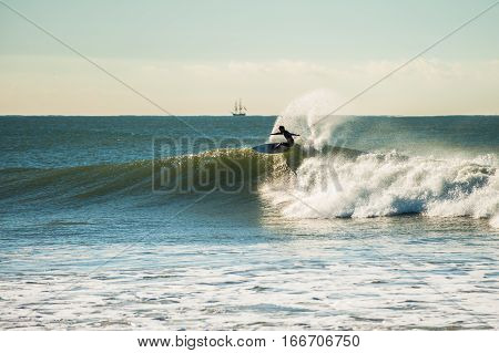 Surfer flying off the wave lip as off shore winds blow.