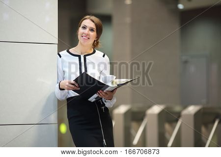 The happy business woman in a white blouse and a black skirt with the open folder standing near the wall in front of turnstiles in business center