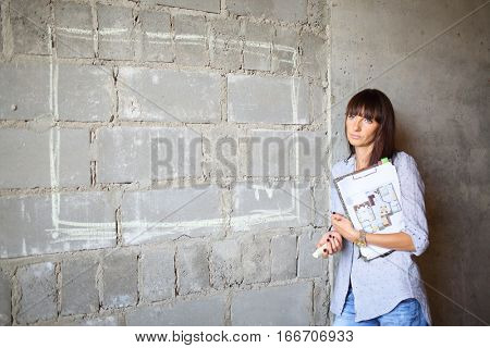Designer with piece of chalk and floor plan standing near the concrete wall with a painted TV on a wall on a construction site