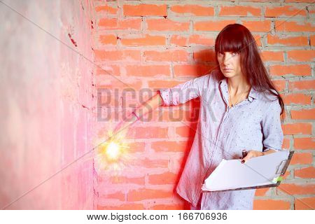 Woman with long hair making marks on the wall using a laser level in a newly built room