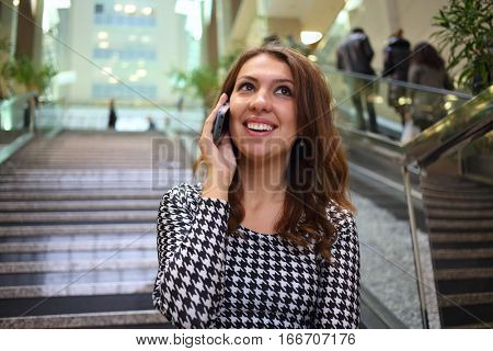 A young woman talking on mobile in front of the marble staircase of the business center