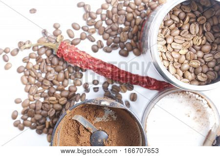 Open grinder with ground coffee. Open jar of coffee beans is close. Coffee beans are scattered on the table. Among them the dried pod of red pepper. On a white background. View from above.