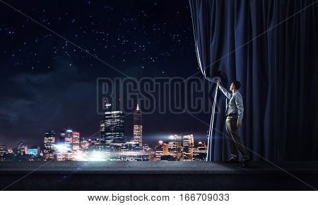 Young businessman opening velvet curtain and presenting modern city view