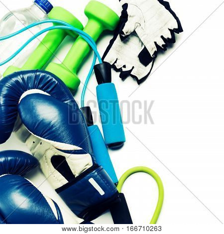 Fitness concept - boxing glove, dumbbells, skipping rope and bottle on the white background