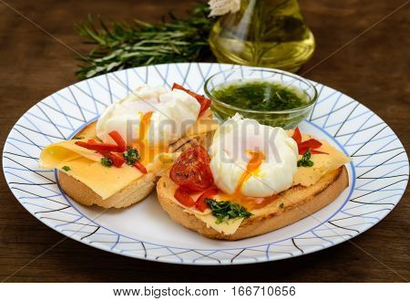 Crispy toast with poached egg cheese peppers tomatoes souse on a plate on a dark wooden background. Close up