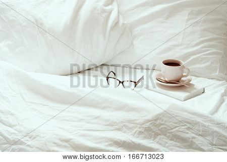 Open white, rumpled bedding with coffee, eyeglasses and book. Room for copy.