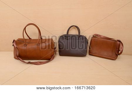 Leather three bag for man isolated on wooden background
