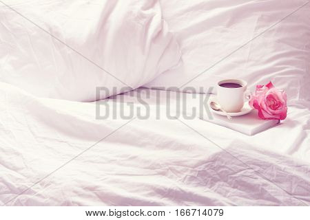 Open white, rumpled bedding with coffee, flower and book. Room for copy.