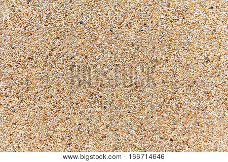 Wall of small sand stone texture. Pebbles and sand wall texture. Sand wall background for design with copy space for text or image.