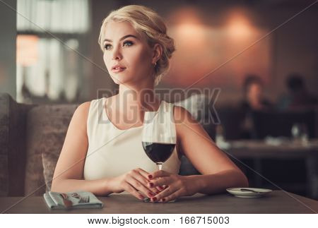 Elegant blonde lady with glass of red wine in restaurant