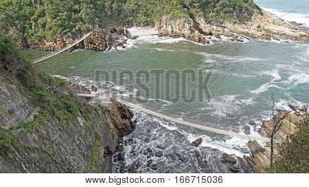 Estuary of the Storms River into the Indian Ocean in the Tsitsikamma National Park in the province of East Cape, two hanging bridges over the estuary of the river, landscape at the Garden Route in South Africa
