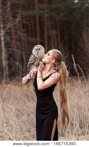 Beautiful woman in a black dress with an owl on his arm. Blonde with long hair in nature holding a owl. Romantic delicate image of a girl