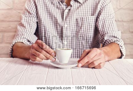 Coffee break. Man sitting on the white table with cup of espresso in the checked shirt. White bricks wall background.