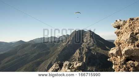 Lonely paraglider over the mountaing range in the summer