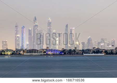 Dubai Marina skyscrapers and residential villas on the Palm Jumeirah at night