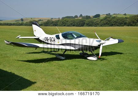 Ocova Slovakia - August 2 2014: Ultralight double-seat propeller-driven PS-28 Cruiser airplane stands on grass landing strip in small country airport