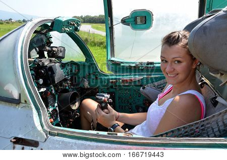 Ocova Slovakia - August 2 2014: Girl sits and smiles in cabin of old jet fighter MiG-21 holding the control stick