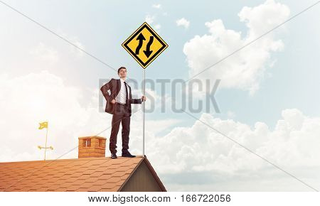 Young businessman standing on house roof and showing yellow roadsign. Mixed media