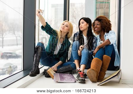 concept of socialization and no discrimination between different ethnic girls using their phones for social media before starting to study