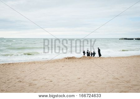 OSTEND BELGIUM - AUGUST 7 2012: Group of jewish child and rabbi on city beach in cold cloudy day