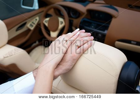 Bridal hands with rings on the leather car seats.