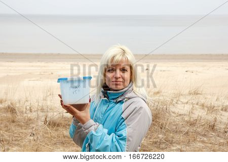 A lady holding a geocaching container at the sea