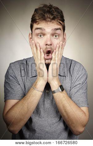 Crazy adult man make surprised faces in studio