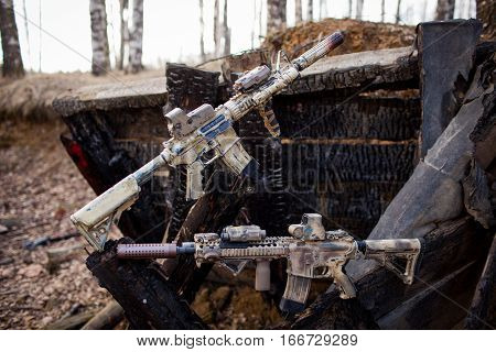 Assault rifles, painted in sand color on the background of the burnt logs. Airsoft.