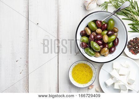 Greek cuisine ingredients: fresh olives mix, feta cheese, rosemary twigs, garlic, peppercorns and olive oil on white wooden background