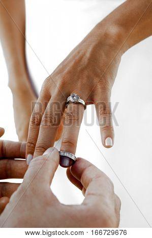 Groom Putting Wedding Band on Bride's Finger