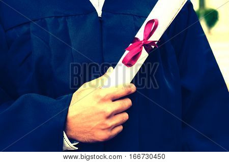 Midsection closeup of young male student holding diploma on graduation day