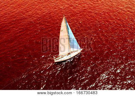 Conceptual shot of sailboat sailing in ocean full of conceptual blood
