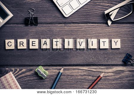 Workspace desk with keyboard office working stuff and wooden elements with the letters collected in the word creativity