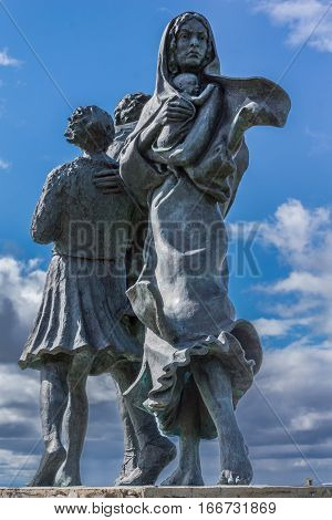 Helmsdale Scotland - June 4 2012: The Emigrant Statue at the south entrance of the town. Closeup of mother holding baby. Back of teenaged boy. Blue sky with white and dark clouds bronze with green spots.