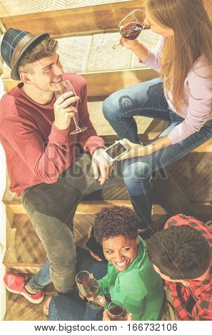 Top view of friends toasting red wine in winery brewery pub - Young people having fun laughing and sitting on wooden stairs in pub restaurant - Focus on left man face - Warm cinematic filter filter