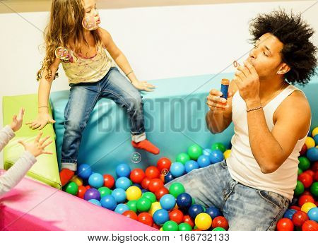 Young father playing with his daughter blowing soap bubbles inside ball pit swimming pool - Happy people having fun in playground - Family and love concept - Focus on man eye - Cinematic filter