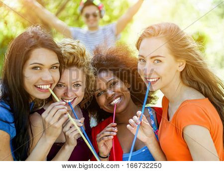 Happy diverse ethnic friends drinking cocktail in summer party outdoor - Young women having fun with dj set - Friendshipvacation and party concept - Focus on center girls - Warm filter with back flare